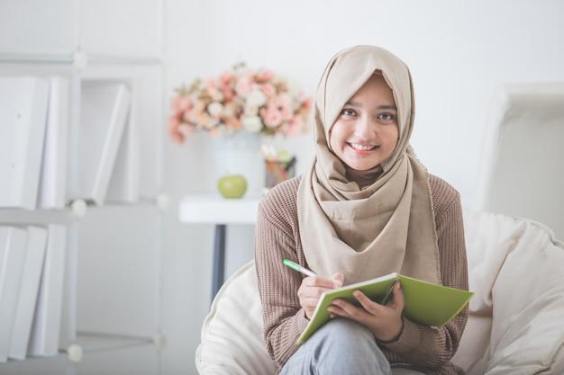 Linda mulher asiática com lenço na cabeça escrevendo algo