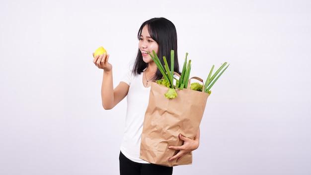 Linda mulher asiática com saco de papel de legumes frescos e segurando limão fresco