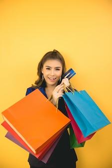 Linda mulher asiática com sacola de compras e cartão de crédito na mão