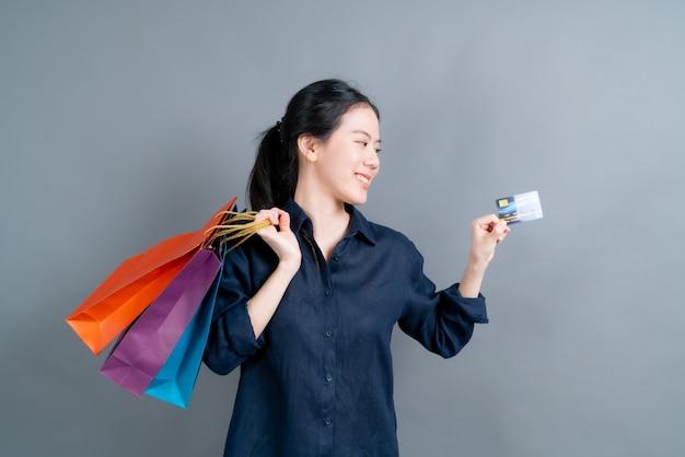 Linda mulher asiática com sacolas de compras e apresentando cartão de crédito isolado em fundo cinza