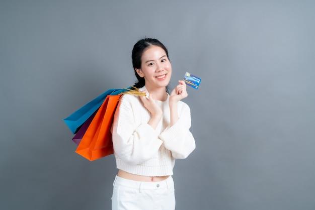 Linda mulher asiática com sacolas de compras e apresentando cartão de crédito isolado na parede cinza