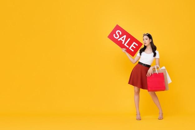 Linda mulher asiática com sacos de compras, mostrando sinal de venda vermelho