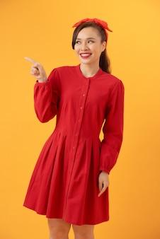 Linda mulher asiática com um vestido vermelho de pé sobre um fundo laranja
