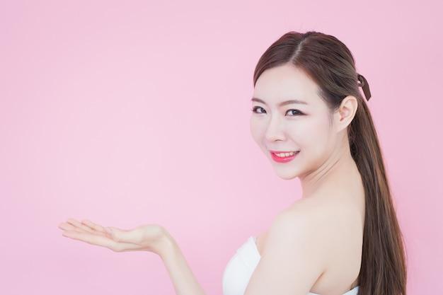 Linda mulher asiática com uma pele perfeita. menina do sorriso que mostra o espaço vazio da cópia que apresenta seu produto
