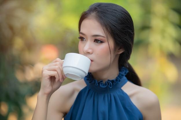 Linda mulher asiática com vestido azul de manhã fresca, bebendo café quente