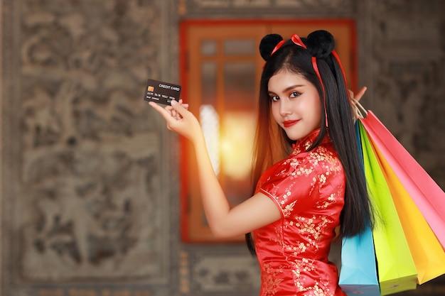 Linda mulher asiática com vestido chinês vermelho tradicional cheongsam qipao com gesto de mostrar o cartão de crédito e segurar sacolas de compras