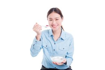 Linda mulher asiática comer iogurte com frutas sobre fundo branco