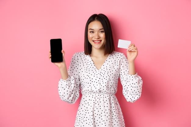 Linda mulher asiática, compras online, mostrando o cartão de crédito do banco e a tela do celular, sorrindo e olhando para a câmera, em pé sobre rosa.