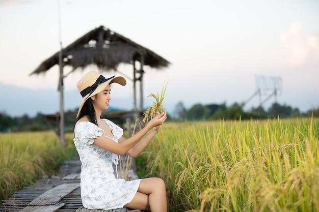Linda mulher asiática curtindo no campo de arroz
