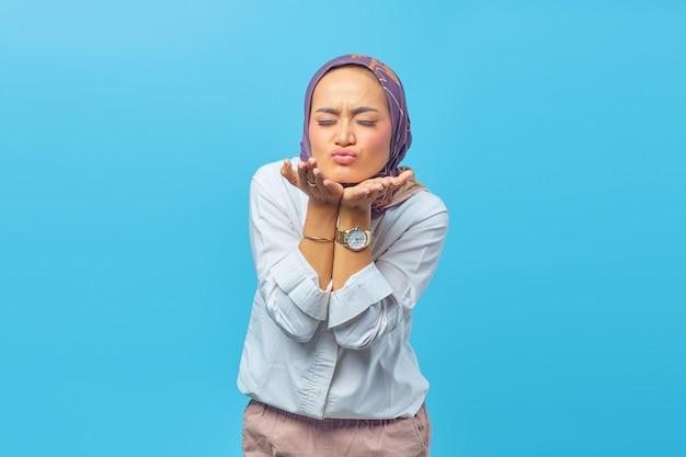 Linda mulher asiática dando beijo no ar. isolado sobre fundo azul. conceito de dia dos namorados.