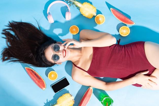 Linda mulher asiática de biquíni vermelho, óculos escuros e deitada com fones de ouvido, telefone e frutas ao redor. conceito de viagens de praia tropical no verão