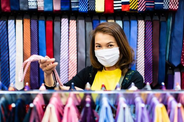 Linda mulher asiática de meia-idade segurando e escolhendo uma gravata colorida na loja