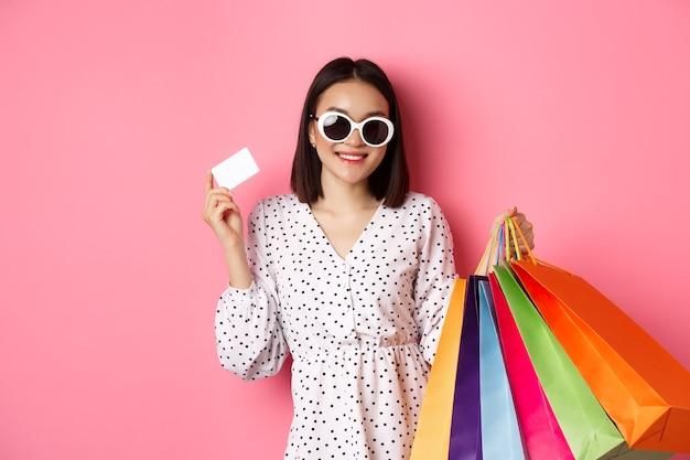 Linda mulher asiática de óculos escuros indo às compras, segurando sacolas e mostrando o cartão de crédito, em pé sobre a rosa