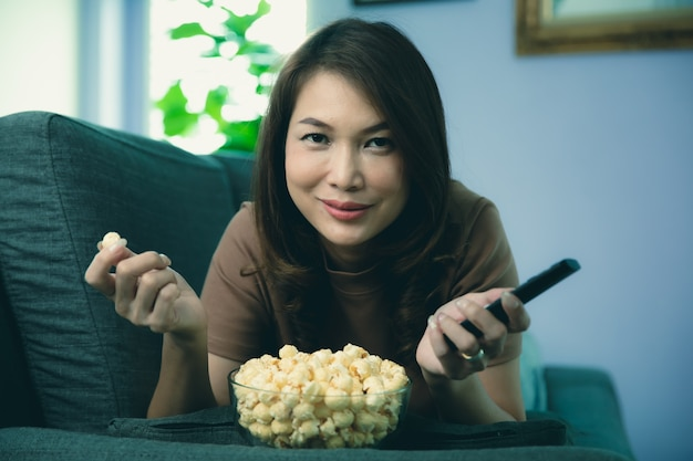 Linda mulher asiática deitada no sofá em relaxar e feliz segurando o controle remoto na mão com tigela de pipoca na sala de estar em casa.
