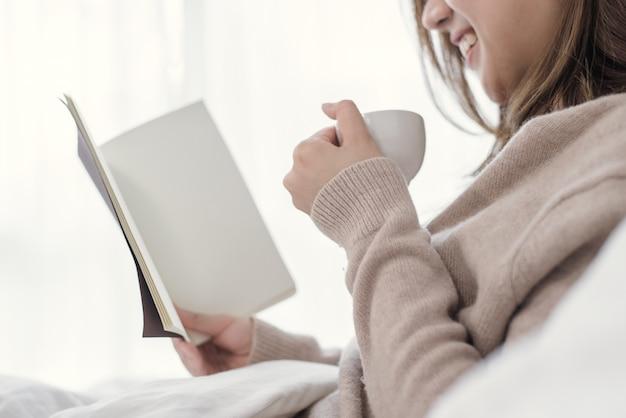 Linda mulher asiática desfrutando de café quente e lendo o livro na cama no quarto dela