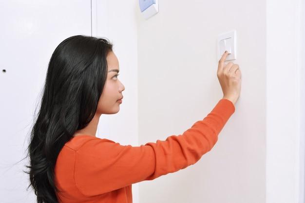Linda mulher asiática desligar a luz com interruptor de parede