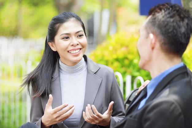 Linda mulher asiática discutindo plano com seu parceiro de negócios