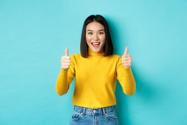 Linda mulher asiática elogia o bom trabalho, mostrando os polegares para cima gesto e sorrindo em aprovação, recomenda o produto, satisfeita em pé sobre o fundo azul.