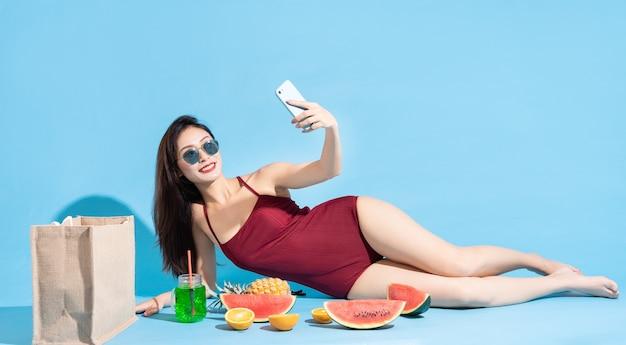Linda mulher asiática em biquíni vermelho, mentindo e usando o telefone para tirar uma selfie com frutas tropicais ao redor. conceito de viagens de praia tropical no verão