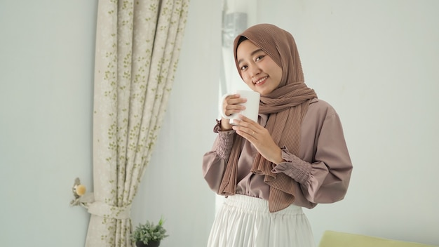 Linda mulher asiática em hijab sorrindo em pé tomando uma bebida em casa