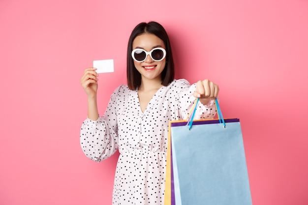 Linda mulher asiática em óculos de sol, vai às compras, segurando sacolas e mostrando o cartão de crédito em pé ...
