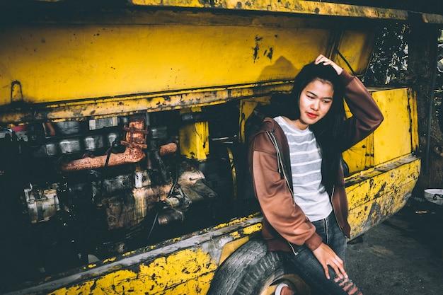 Linda mulher asiática em pé ao lado do motor do carro