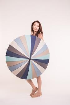Linda mulher asiática em pé com guarda-chuva listrado na parede branca.