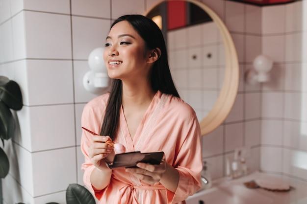 Linda mulher asiática em roupão de seda segurando paleta com cosméticos e escova