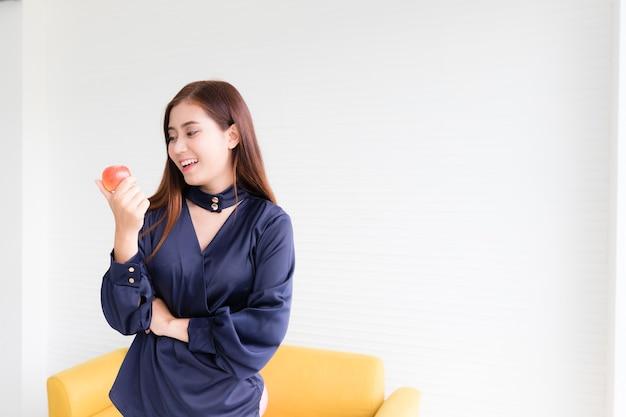 Linda mulher asiática em roupas casuais pegando e olhando para uma maçã