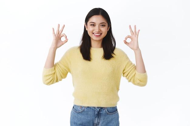 Linda mulher asiática em suéter amarelo mostrando bom gesto e sorrindo satisfeita, recomendo ótimo atendimento, dizendo tudo bem, tudo bem, concordo com amigo, sorrindo