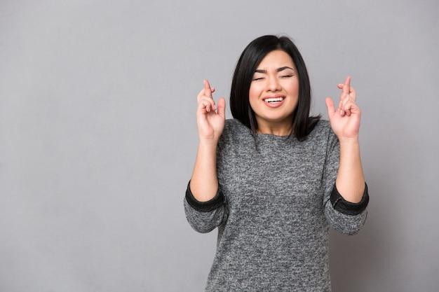 Linda mulher asiática em suéter cinza com os dedos cruzados e olhos fechados