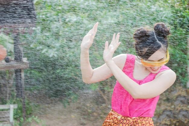 Linda mulher asiática em traje tradicional da tailândia, jogando água em songkran festiva
