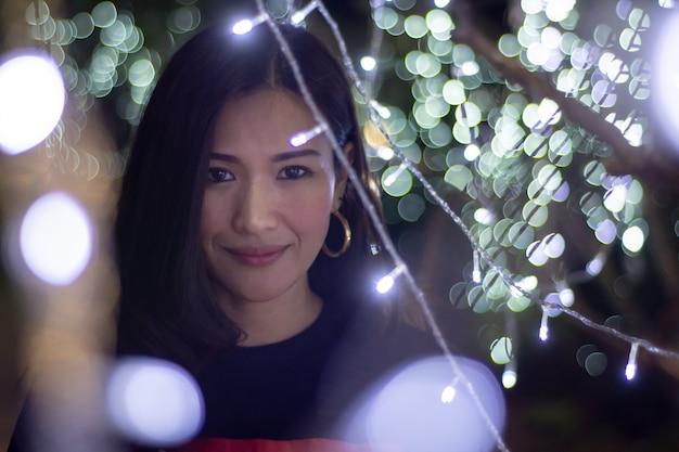 Linda mulher asiática em um fundo com luzes de cor de bokeh