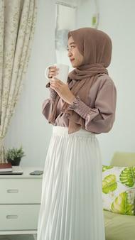 Linda mulher asiática em um hijab em pé desfrutando de uma bebida em casa