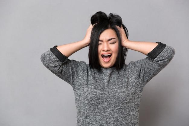 Linda mulher asiática em um macacão cinza gritando e segurando a cabeça com as duas mãos com os olhos fechados