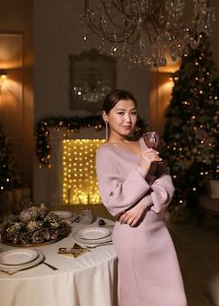 Linda mulher asiática em um vestido luxuoso bebendo vinho em uma taça olhando para a câmera