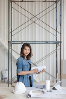 Linda mulher asiática engenheiro na camisa azul jeans em pé e escrevendo