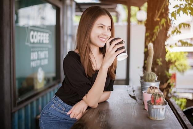 Linda mulher asiática está a beber café