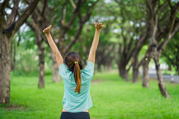 Linda mulher asiática está exercitando no parque.