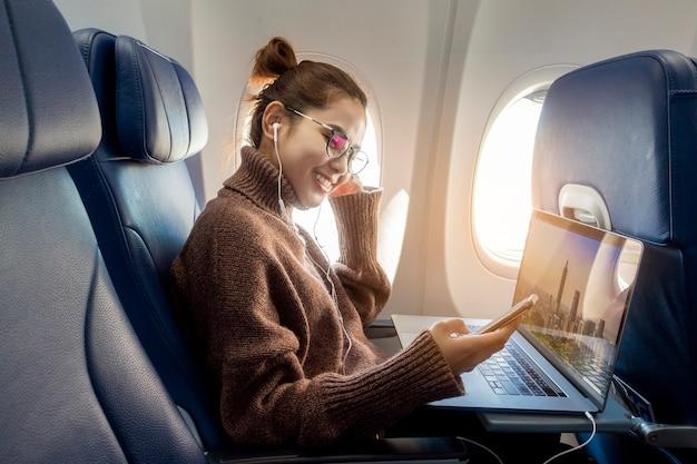 Linda mulher asiática está trabalhando com o laptop no avião