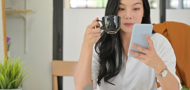 Linda mulher asiática está verificando mensagens em um smartphone e tomando café em um escritório confortável.