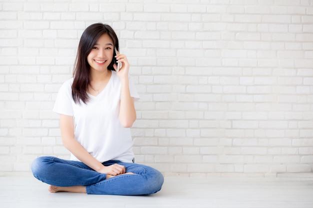 Linda mulher asiática fala telefone inteligente e sorriso