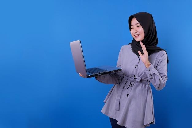 Linda mulher asiática falando alguma coisa com o laptop