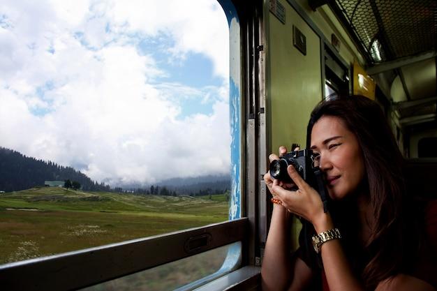 Linda mulher asiática faz uma foto através da janela do trem