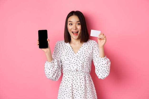 Linda mulher asiática fazendo compras online, mostrando o cartão de crédito do banco e a tela do celular, sorrindo e olhando para a câmera
