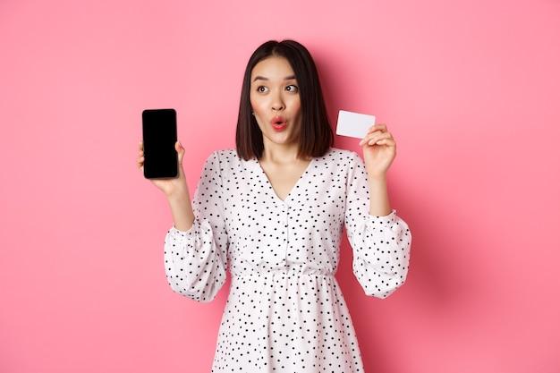 Linda mulher asiática fazendo compras online, mostrando o cartão de crédito do banco e a tela do celular, sorrindo e olhando para a esquerda no espaço da cópia