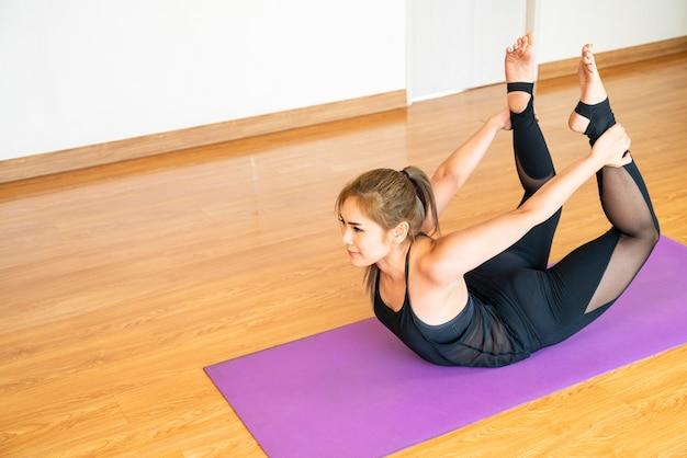 Linda mulher asiática fazendo exercícios de treino de poses de ioga para relaxar e meditar em casa. ásia, yoga, zen, esporte, fitness. saudável, atividade doméstica ou conceito de mulher asiática