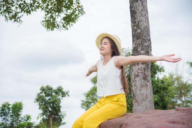 Linda mulher asiática fazendo mãos estendidas e sorriso com boa natureza na floresta