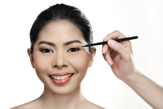 Linda mulher asiática fazendo maquiagem