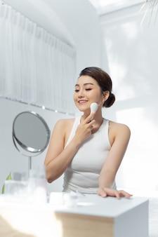 Linda mulher asiática fazendo tratamento de pele sozinha em casa. facial galvânico